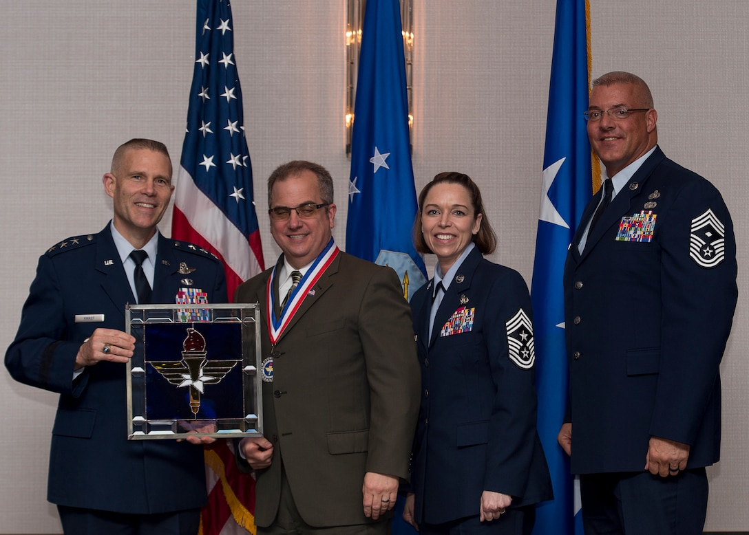 """Joseph M. DiMisa, Instructor of Environmental Management at the Air Force Institute of Technology at Wright-Patterson Air Force Base, Ohio, receives the 2017 Non-supervisory Civilian of the Year Award from Lt. Gen. Steve Kwast, Commander of AETC, during the AETC 12 Outstanding Airmen of the Year Awards banquet Feb. 22, 2018 in Orlando, Fla. DiMisa directed eight AFIT Civil Engineering courses, while teaching 130 instructional hours in 25 courses, educating 783 Department of Defense engineers, developed seven Air Force level on-demand environmental management mini-courses, which are used 8,000 times per month and saved the Air Force $400,000 annually, as well as authored and published """"Ecological Restoration of the Midwest"""" a 296 page book and a first of its kind for the Midwest. (U.S. Air Force photo by Staff Sgt. Kenneth W. Norman)"""