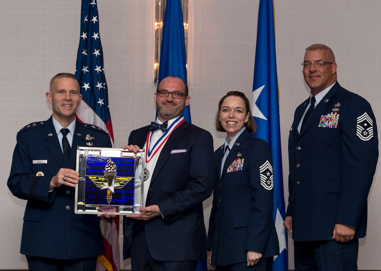 Dr. Andrew M. Akin, Professor of National Security Studies at the Air Command and Staff College at Maxwell-Gunter Air Force Base, Alabama, receives the 2017 Non-supervisory Civilian of the Year Award from Lt. Gen. Steve Kwast, Commander of AETC, during the AETC 12 Outstanding Airmen of the Year Awards banquet Feb. 22, 2018 in Orlando, Fla. Akin created and assisted seven academic courses, while teaching three courses, transforming Official Professional Military Education (OPME) content for 28,000 Air Force, civilian and joint service students winner of the Minerva Research Grant, as well as chaired an innovation team, producing the first-ever Facebook live and ADOBE Connect live webinars for OPME students. (U.S. Air Force photo by Staff Sgt. Kenneth W. Norman)