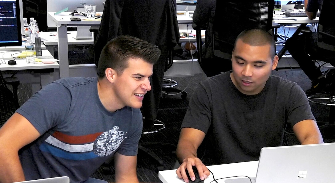 Capt. Bryon Kroger, left, and 1st Lt. Carlo Viray, right, review combat applications in Cambridge, Massachusetts, Aug. 13, 2017. The officers, who are part of the Air Force's Air Operations Center Pathfinder acquisition program run out of Hanscom Air Force Base, Massachusetts, work with coders in an open workspace environment with civilians who train them on the techniques used by Silicon Valley's best software programmers. (U.S. Air Force photo by Rick Berry)