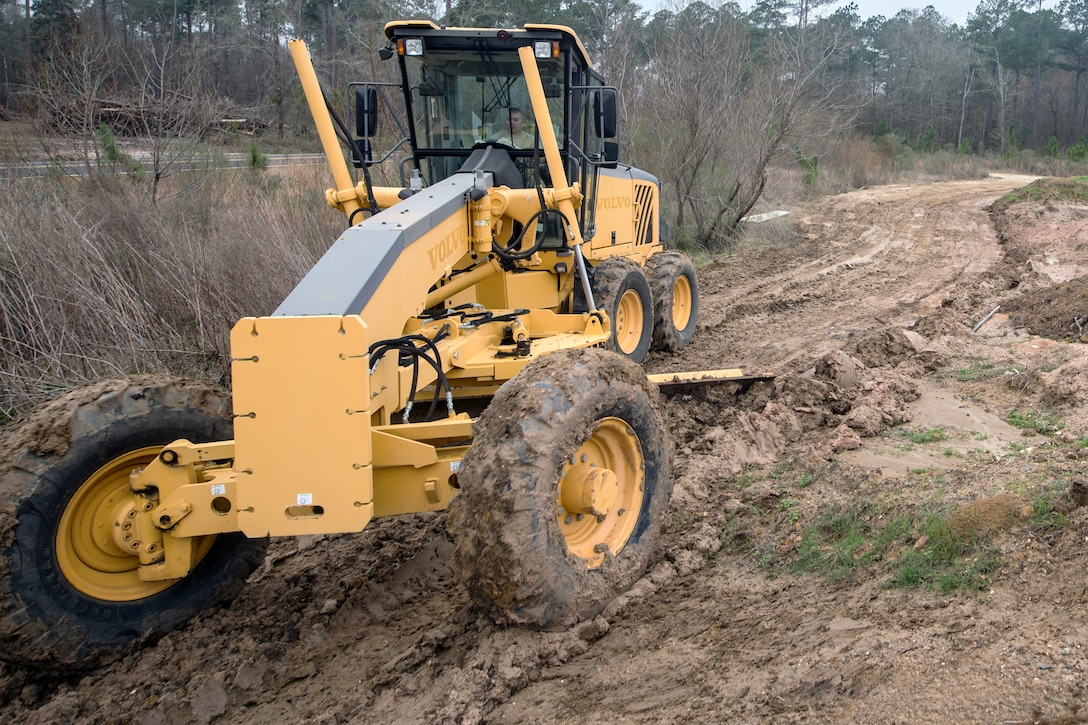 Staff Sgt. Elliot Westerman, 23d Civil Engineer Squadron (CES) heavy equipment operator, pushes dirt with a grader, Feb. 15, 2018, at Moody Air Force Base, Ga. Airmen from the 23d CES participated in a Prime Base Engineer Emergency Force training day to prepare for some of the wartime tasks they could encounter while in a deployed environment. (U.S. Air Force photo by Airman Eugene Oliver)