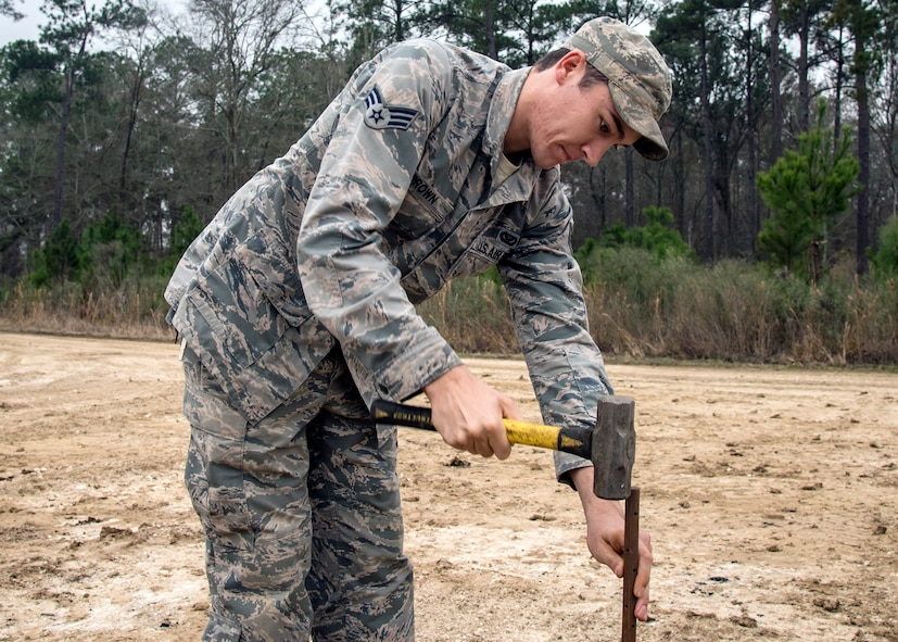 Senior Airman Davon Brown, 23d Civil Engineer Squadron pavements and equipment specialist, hammers a post into the ground, Feb. 15, 2018, at Moody Air Force Base, Ga.  Airmen from the 23d CES participated in a Prime Base Engineer Emergency Force training day to prepare for some of the wartime tasks they could encounter while in a deployed environment. (U.S. Air Force photo by Airman Eugene Oliver)