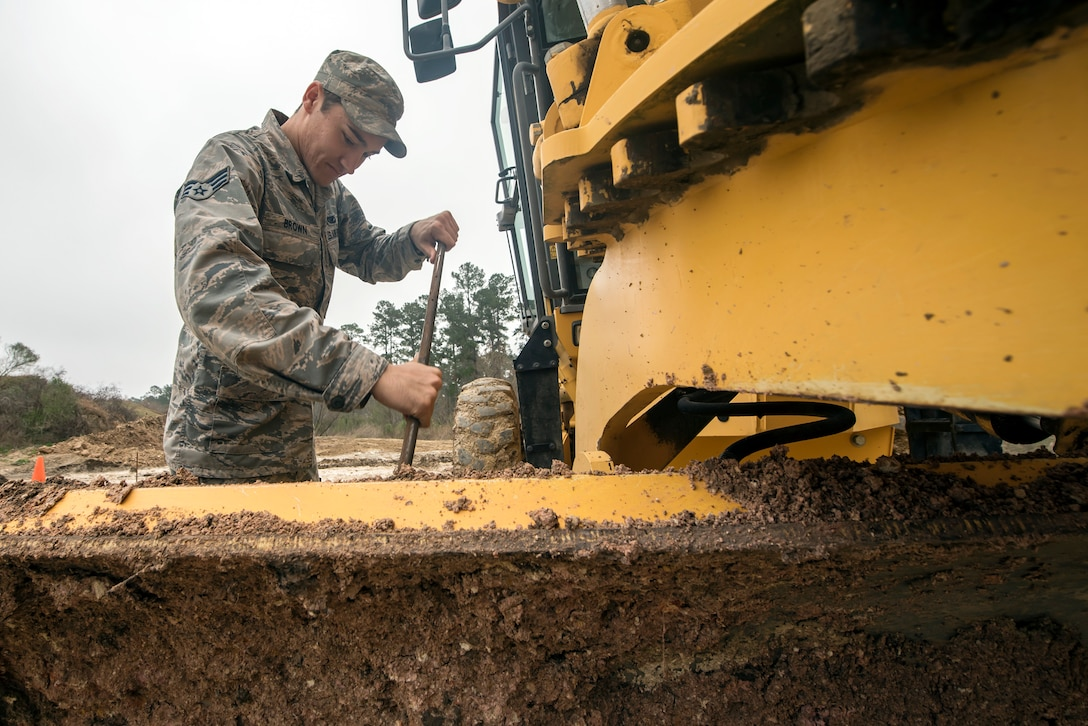 Senior Airman Davon Brown, 23d Civil Engineer Squadron pavements and equipment specialist, cleans dirt off the blade of a grader, Feb. 15, 2018, at Moody Air Force Base, Ga. Airmen from the 23d CES participated in a Prime Base Engineer Emergency Force training day to prepare for some of the wartime tasks they could encounter while in a deployed environment. (U.S. Air Force photo by Airman Eugene Oliver)