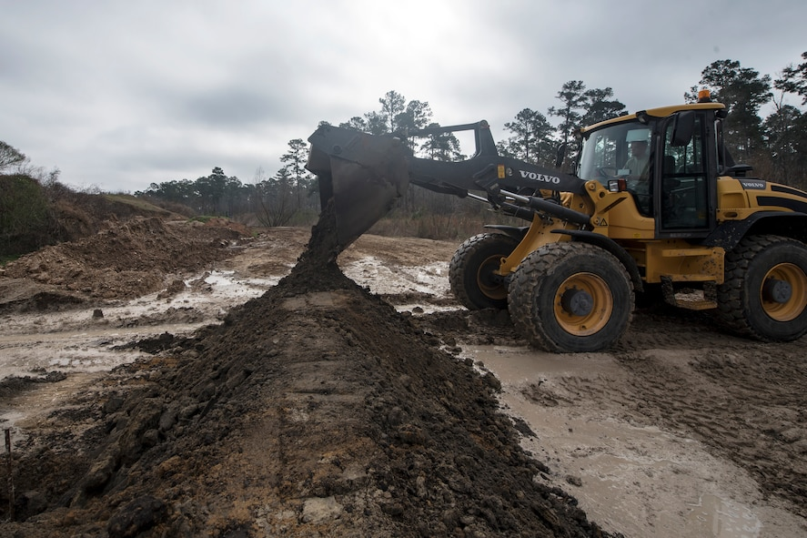 A loader drops dirt on a bern, Feb. 15, 2018, at Moody Air Force Base, Ga. Airmen from the 23d CES participated in a Prime Base Engineer Emergency Force training day to prepare for some of the wartime tasks they could encounter while in a deployed environment. (U.S. Air Force photo by Airman Eugene Oliver)