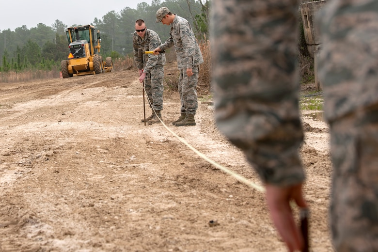 Airmen from the 23d Civil Engineer Squadron measure out the perimeter for a bern, Feb. 15, 2018, at Moody Air Force Base, Ga. Airmen from the 23d CES participated in a Prime Base Engineer Emergency Force training day to prepare for some of the wartime tasks they could encounter while in a deployed environment. (U.S. Air Force photo by Airman Eugene Oliver)