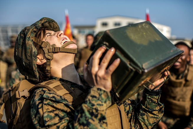A Marine closes her eyes and tilts her face upward while trying to lift an ammo can, as fellow troops watch.