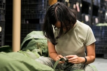 Airman Lore Anne Calimlim, 23d Logistics Readiness Squadron (LRS) aircraft parts store apprentice, removes tags from A-bags in preparation for a Phase 1 exercise, Feb. 23, 2018, at Moody Air Force Base, Ga. The 23d LRS prepped approximately 400 A-bags, which consisted of items essential for deploying Airmen. This helped ensure the success of the Airmen participating in the exercise, which tested operations, maintenance and logistics to demonstrate the 23d Wing's ability to rapidly deploy to meet the needs of combatant commanders. (U.S. Air Force photo by Airman 1st Class Erick Requadt)