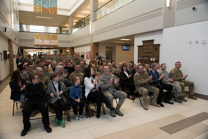 Military members and civilians applaud during the 27th Special Operations Medical Group building ribbon cutting ceremony at Cannon Air Force Base, N.M., Feb. 23, 2018. This upgrade has been planned for the last few years. The ground-breaking ceremony was July of 2015 and now, nearly three years later, the building complete and open for patients. (U.S. Air Force photo by Staff Sgt. Michael Washburn/Released)