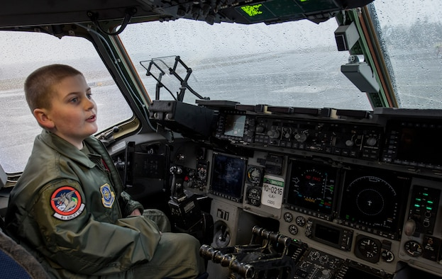 McKay Neel, McChord's newest Pilot for a Day participant, sits in the pilot seat of a C-17 Globemaster III during his tour of McChord Field at Joint Base Lewis-McChord, Wash., Feb. 20, 2018. During his day as a 4th Airlift Squadron pilot, McKay visited military working dogs; the fire department; survival, evasion, resistance and escape training office; a C-17 Globemaster III simulation and received of tour of a C-17. (U.S. Air Force photo by Senior Airman Tryphena Mayhugh)