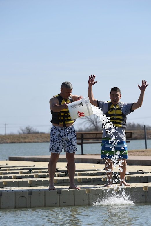 U.S. Air Force Col. Alex Ganster, 17th Training Group commander, and U.S. Army Lt. Col. Yukio Kuniyuki, 344th Military Intelligence Battalion commanding officer, pour ice into Lake Nasworthy to kick off the swim portion of the Polar Bear Plunge event hosted by the 17th Force Support Squadron in San Angelo, Texas, Feb. 24, 2018. Service members and their families had the opportunity to brave the water and compete for the coveted trophy of most participants from a unit. (U.S. Air Force photo by Airman 1st Class Seraiah Hines/Released)