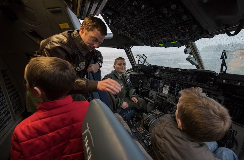 Capt. Hatton Updike, 4th Airlift Squadron pilot, tells McKay Neel (back right), McChord's newest Pilot for a Day participant, and two friends about the features of a C-17 Globemaster III during a McChord Field tour at Joint Base Lewis-McChord, Wash., Feb. 20, 2018. McKay, along with his family and friends, spent the day learning about life at as an Airman and ended it with cake and ice cream at the 4th Airlift Squadron. (U.S. Air Force photo by Senior Airman Tryphena Mayhugh)