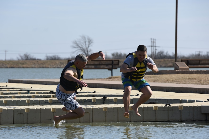 U.S. Air Force Col. Alex Ganster, 17th Training Group commander, and U.S. Army Lt. Col. Yukio Kuniyuki, 344th Military Intelligence Battalion commanding officer, take the first jump into Lake Nasworthy to start the swim portion of the Polar Bear Plunge in San Angelo, Texas, Feb. 24, 2018. Despite it being 72 degrees out, many participants said that the water was chilly. (U.S. Air Force photo by Airman 1st Class Seraiah Hines/Released)