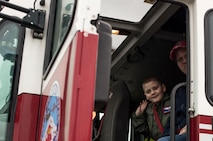 McKay Neel, McChord's newest Pilot for a Day participant, sits inside a fire truck with his dad during a tour of McChord Field at Joint Base Lewis-McChord, Wash., Feb. 20, 2018. The Pilot for a Day program invites children with serious or chronic conditions of all ages, military or civilian, to be a guest at the 62nd Airlift Wing and one of McChord Field's flying squadrons for a day. (U.S. Air Force photo by Senior Airman Tryphena Mayhugh)