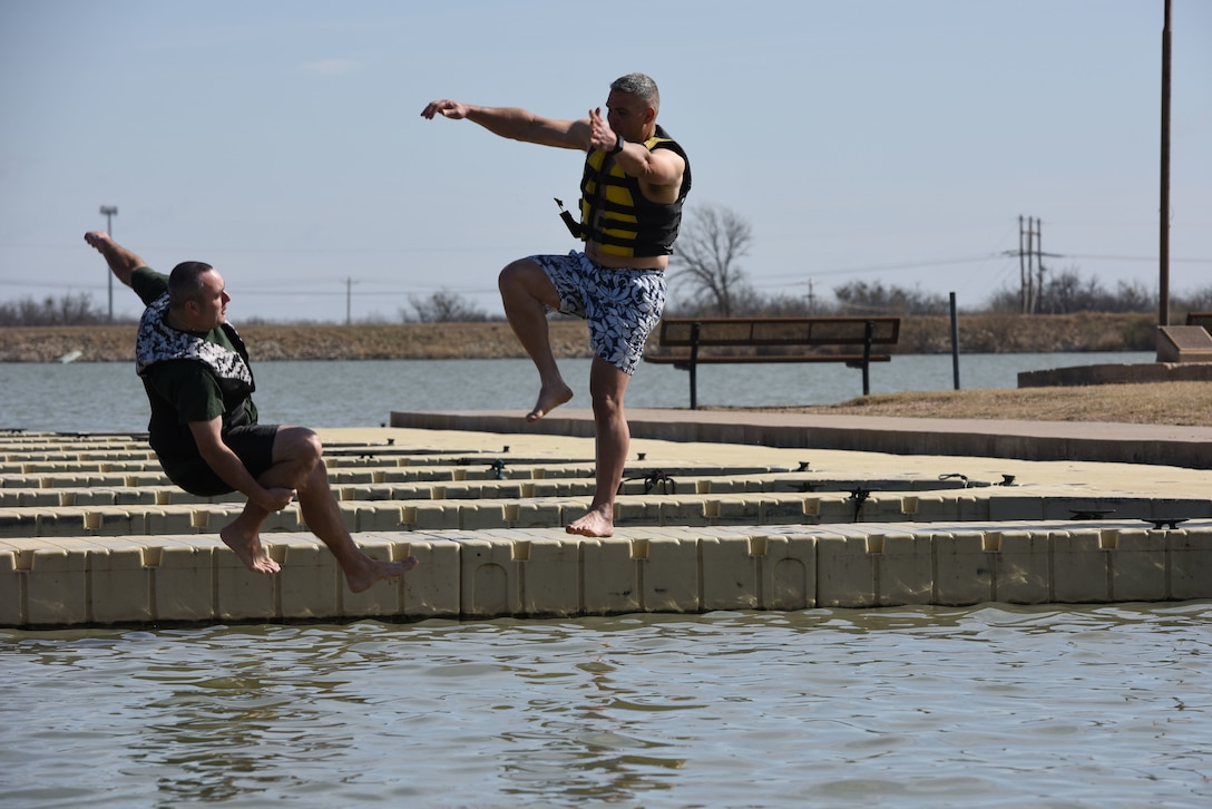 U.S. Air Force Chief Master Sgt. Daniel Stein, 17th Training Group superintendent, and Col. Alex Ganster, 17th TRG commander, represent the 17th TRG during the Polar Bear Plunge event hosted by the 17th Force Support Squadron at Lake Nasworthy in San Angelo, Texas, Feb. 24, 2018. After taking the plunge, service members could warm up by a fire while roasting s'mores. (U.S. Air Force photo by Airman 1st Class Seraiah Hines/Released