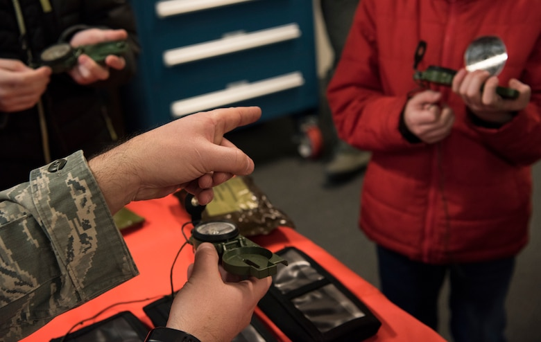 Staff Sgt. David Bowden, 62nd Operational Support Squadron noncommissioned officer in charge of survival, evasion, resistance and escape training, demonstrates how to use a compass to children participating in McChord Field's Pilot for a Day program at Joint Base Lewis-McChord, Wash., Feb. 20, 2018. While undergoing SERE training, McKay Neel, McChord's newest Pilot for a Day participant, had the opportunity to use a simulator to steer a parachute onto a ship. (U.S. Air Force photo by Senior Airman Tryphena Mayhugh)