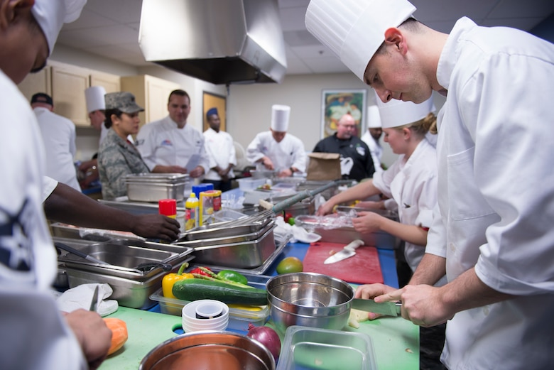 Chefs square off against each other by preparing meals in the Community Commons kitchen during the 2018 Grill Master competition at Luke Air Force Base, Ariz., Feb. 23, 2018. The Grill Master competition invited teams of two Airmen from units across the base to cook the best meal they could make out of fresh ingredients and a unique secret ingredient assigned to each team. (U.S. Air Force photo/Senior Airman Ridge Shan)