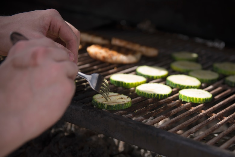 A competitor flips zucchini on the grill during the 2018 Grill Masters competition at Luke Air Force Base, Ariz., Feb. 23, 2018. The competition involved teams of two from across the base competing to grill the best meal. (U.S. Air Force photo/Senior Airman Ridge Shan)