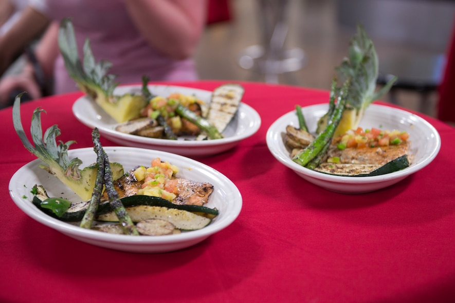 The winning meal of the 2018 Grill Masters competition - wood-fired grilled salmon with pineapple salsa, asparagus and vegetables – sits on display prior to judging at Luke Air Force Base, Ariz., Feb. 23, 2018. Each team was required to incorporate a secret ingredient, in this case pineapple, into a meal consisting of one meat and two sides. (U.S. Air Force photo/Senior Airman Ridge Shan)