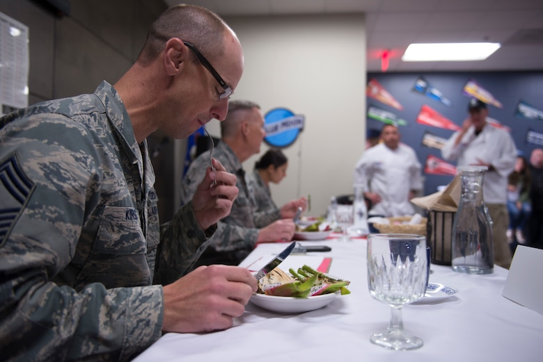 From front to back: Chief Master Sgt. Todd Kirsch, 56th Mission Support Group command chief, Col. Robert Sylvester, 56th Mission Support Group commander, and Maj. Maritzel Castrellon, 56th Force Support Squadron commander, judge a prepared dish during the 2018 Grill Masters competition while the chefs, Drake Montoya and Patrick Campbell, Airman and Family Readiness Center employees, look on nervously at Luke Air Force Base, Ariz., Feb. 23, 2018. Montoya and Campbell placed third.