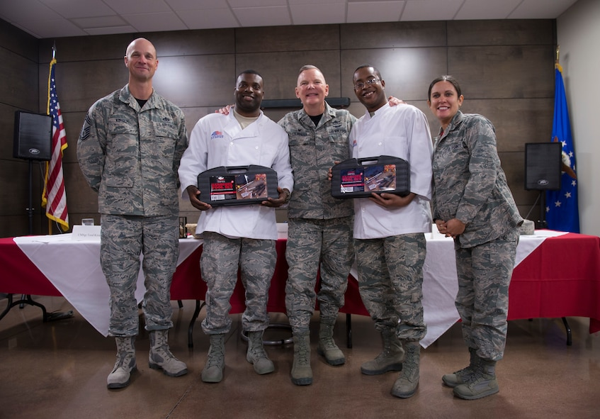Chief Master Sgt. Todd Kirsch, Col. Robert Sylvester, and Maj. Maritzel Castrellon, judges for the 2018 Grill Master competition, pose with the winners of the competition, Staff Sgt. Victor McKinnon, 607th Air Control Squadron surveillance technician and Staff Sgt. Justin Williams, 607th ACS weapons director at Luke Air Force Base, Ariz., Feb. 23, 2018. McKinnon and Williams beat out four other two-man teams in the competition, which required them to cook a meal with one meat and two sides, while incorporating a secret ingredient. (U.S. Air Force photo/Senior Airman Ridge Shan)