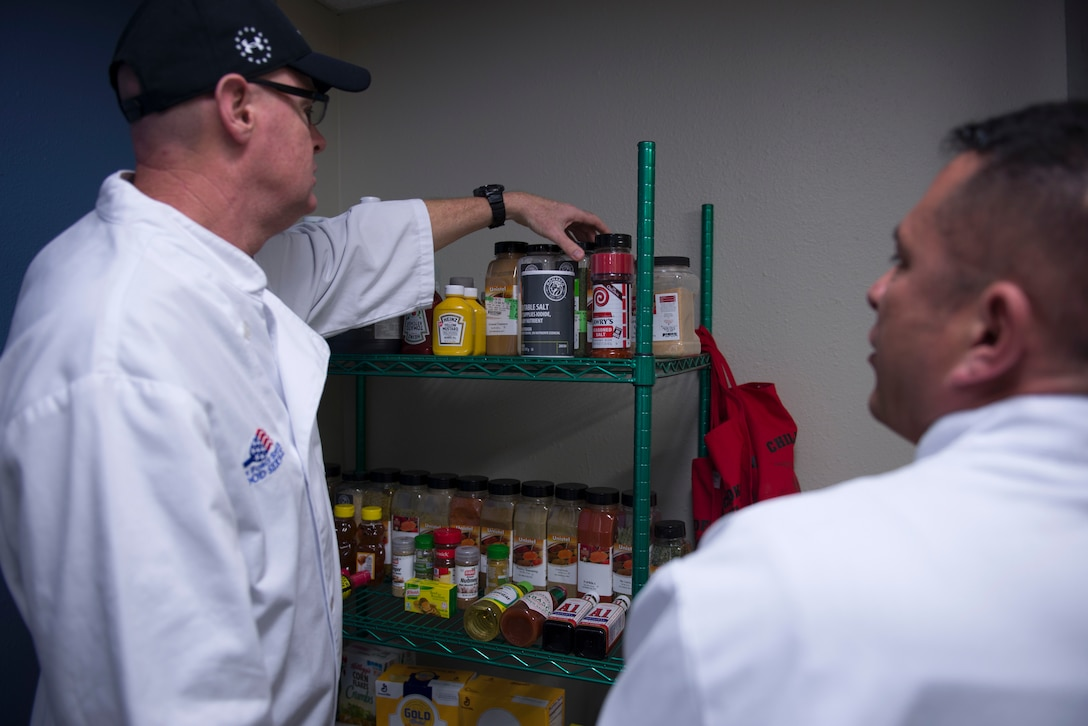 Patrick Campbell and Drake Montoya, forming a two-man team from the Airman and Family Readiness Center, searches through seasonings during the 2018 Grill Master competition at Luke Air Force Base, Ariz., Feb. 23, 2018. The competition challenged Airmen to craft a meal for judging from a slew of fresh produce, meat, and a unique secret ingredient. (U.S. Air Force photo/Senior Airman Ridge Shan)