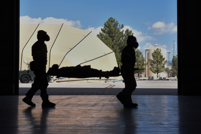 Airmen from the 49th Maintenance Group litter carry a simulated casualty during a phase II exercise at Holloman Air Force Base, N.M., Feb. 22, 2018. The participating Airmen's training included donning mission oriented protective posture gear, conducting SABC to simulated injuries while keeping accountability of each other. (U.S. Air Force photo by Staff Sgt. Timothy Young)