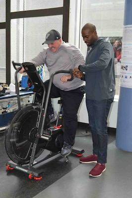 Man rides exercise bike while physical therapist watches.