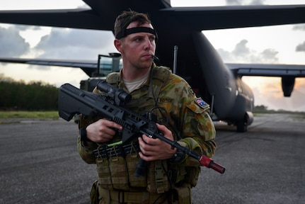 A Royal Australian Air Force security forces member protects an C-130J Super Hercules during a training scenario at exercise COPE NORTH 18 on Tinian, U.S. Commonwealth of the Northern Marianas Islands, Feb. 20. COPE NORTH enables U.S. and allied forces to train humanitarian assistance/disaster relief operations from austere operating bases, enhancing our capacity and capability to respond in times of crisis. (U.S. Air Force photo by Airman 1st Class Christopher Quail)