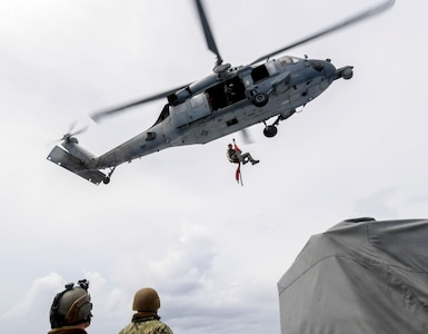 "Naval Air Crewman (Helicopter) 2nd Class Spencer Kachele, assigned to the ""Island Knights"" of Helicopter Sea Combat Squadron (HSC) 25, is lowered by an MH-60S Sea Hawk helicopter to a Mark VI patrol boat manned by Coastal Riverine Squadron 4, Det. Guam, during a joint search and rescue exercise with U.S. Coast Guard Sector Guam, Feb. 23, 2018."
