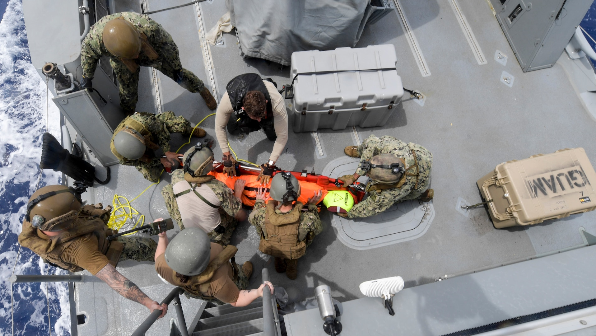 Coastal Riverine Squadron (CRS) 4, Det. Guam and Helicopter Sea Combat Squadron (HSC) 25 Sailors load a search and rescue (SAR) dummy onto a litter aboard a Mark VI patrol boat during a joint SAR exercise with U.S. Coast Guard Sector Guam, Feb. 23, 2018.