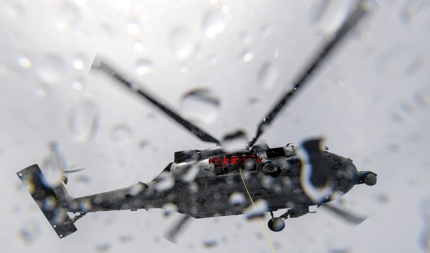 An MH-60S Sea Hawk helicopter, assigned to Helicopter Sea Combat Squadron (HSC) 25, hovers above a Mark VI patrol boat, assigned to Coastal Riverine Group 1, during a joint search and rescue exercise with U.S. Coast Guard Sector Guam, Feb. 23, 2018.