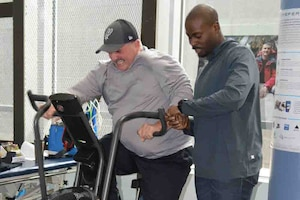 A man rides an exercise bike while a trainer stands next to him.