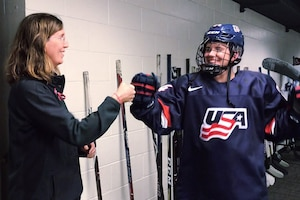 A woman fist bumps a female hockey player.