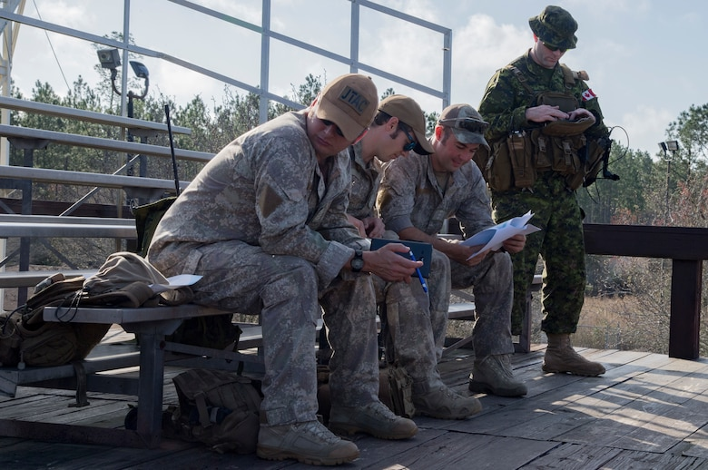 A group of Canadian Royal Air Force and New Zealand army joint terminal attack controllers discuss mission planning prior to combined training, Feb. 21, 2018, at Moody Air Force Base, Ga. Ally forces from the CRAF and NZA traveled to Moody AFB to train with the 75th Fighter Squadron on close air support. (U.S. Air Force photo by Staff Sgt. Eric Summers Jr.)
