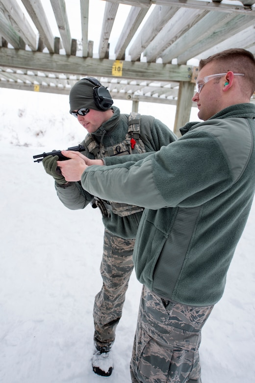 U.S. Air Force Tech. Sgt. Brandon Dahl, left, a combat arms training and maintenance instructor with the 133rd Security Forces Squadron, observes the chamber of an M9 Beretta pistol in Coon Rapids, Minn., Feb. 23, 2018.