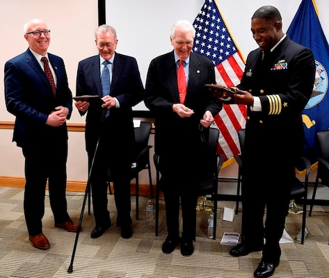 IMAGE: DAHLGREN, Va. (Feb. 22, 2018) – Capt. Godfrey 'Gus' Weekes, right, Naval Surface Warfare Center Dahlgren Division commanding officer, and Donald McCormack, left, executive director of the Naval Surface and Undersea Warfare Centers, present commemorative plaques to retired Adm. James Hogg, second from left, and Dr. Hans Mark, during an electromagnetic railgun line naming ceremony. As public servants, Hogg and Mark laid the foundation for the U.S. Navy Railgun Program and led the effort to explore and illustrate to senior leadership the warfighting advantages of this game-changing technology and were pivotal in gaining the initial funding necessary to demonstrate its feasibility. (U.S. Navy photo by John F. Williams/Released)