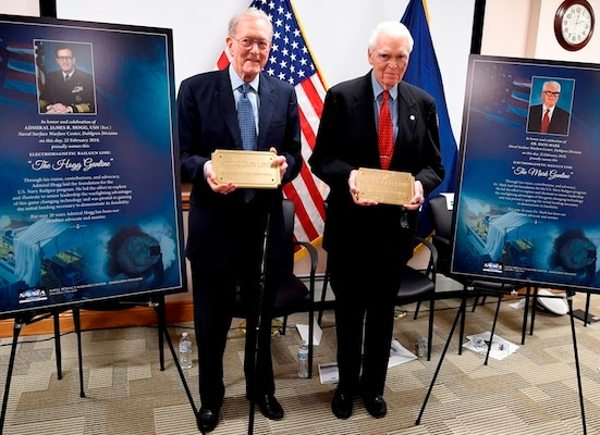 IMAGE: DAHLGREN, Va. (Feb. 22, 2018) – Retired Adm. James Hogg, left, and Dr. Hans Mark pose with the plaques that bear their names and will be installed on the electromagnetic railgun line at Naval Surface Warfare Center Dahlgren Division. As public servants, Hogg and Mark laid the foundation for the U.S. Navy Railgun Program and led the effort to explore and illustrate to senior leadership the warfighting advantages of this game-changing technology and were pivotal in gaining the initial funding necessary to demonstrate its feasibility. (U.S. Navy photo by John F. Williams/Released)