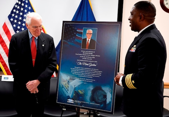 IMAGE: DAHLGREN, Va. (Feb. 22, 2018) – Capt. Godfrey 'Gus' Weekes, right, Naval Surface Warfare Center Dahlgren Division commanding officer, looks over a commemorative poster with Dr. Hans Mark, who along with retired Adm. James Hogg, were honored during an electromagnetic railgun line naming ceremony. As public servants, Hogg and Mark laid the foundation for the U.S. Navy Railgun Program and led the effort to explore and illustrate to senior leadership the warfighting advantages of this game-changing technology and were pivotal in gaining the initial funding necessary to demonstrate its feasibility. (U.S. Navy photo by John F. Williams/Released)