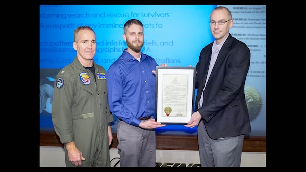 "Defense Contract Management Agency Boeing St. Louis Commander Navy Capt. Paul Filardi and his Quality Assurance Director Steve Santel present Quality Assurance Specialist Ryan Maichel (center) with a commendation signed by Missouri Gov. Eric Greitens ""for his selfless actions in performing search and rescue operations and disaster relief in response to Hurricane Harvey."" (Photo courtesy of DCMA Boeing St. Louis)"