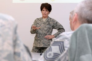An Air Force officer talks to a group of enlisted airmen.