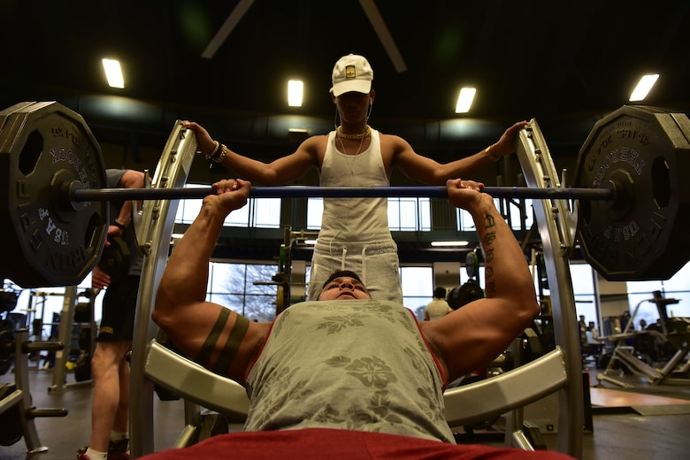 Man does inclined bench press, while another man stands over him.