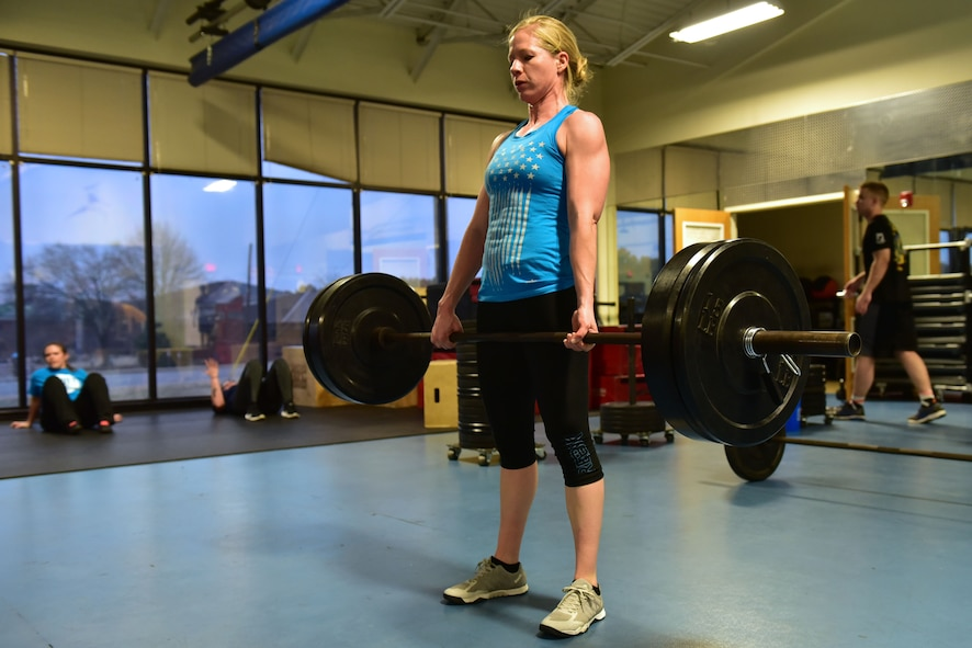 Woman does deadlifts.