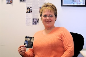 A person holds a photo in her office.