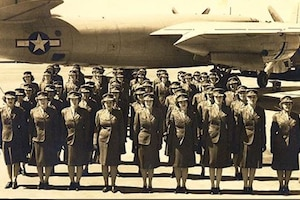 Marines stand in formation in front of an aircraft.