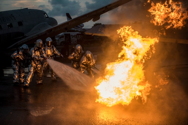 Military firefighters extinguish an aircraft fire during a training exercise.