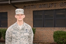 Man in uniform standing in front of his headquarters building.