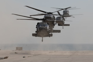 Four military helicopters prepare to land at a base in Kuwait.
