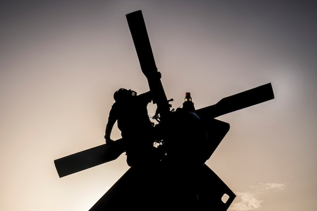 A sailor, shown in silhouette, inspects a helicopter's tail rotor.