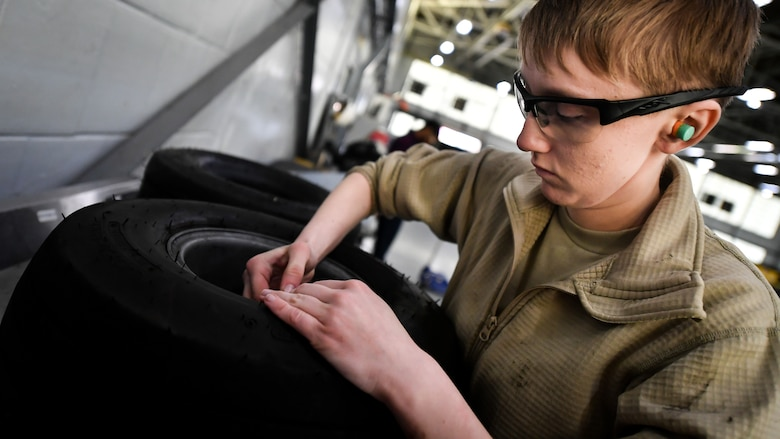 Airman Abigail Weber, 2nd Maintenance Squadron aerospace ground equipment technician, releases air from a bomb loader vehicle tire at Barksdale Air Force Base, La., Feb. 27, 2018. Tires that are found to have defects are replaced.