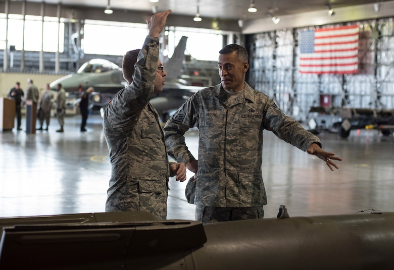 U.S. Air Force Senior Airman Robert Carter, left, a 35th Maintenance Group weapons load crew member, showcases displayed munitions to Chief Master Sgt. Terrence A. Greene, right, the United States Forces Japan and Fifth Air Force command chief, during his tour at Misawa Air Base, Japan, Feb. 23, 2018. Greene stressed the importance of Airmen knowing their mission and how their individual actions contribute to stability across the region. (U.S. Air Force photo by Airman 1st Class Collette Brooks)