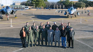 Defense Contract Management Agency Lockheed Martin Fort Worth's flight operations team is led by Marine Corps Lt. Col. Joe Hutcheson (back row, first from left). The team provides program support and worldwide delivery for the F-35 Lightning II, the F-16 Fighting Falcon and the F-22 Raptor. It is a global effort supported by eight active duty service members, multiple civilians and two Air Force Reserve officers — Lt. Col. Michael Kirk (front row, third from left) and Maj. Kerry McAnally (back row, fourth from left). According to leadership, the pair play a vital role within the mission. (Photo courtesy of Lockheed Martin Aeronautics-Angel DelCueto)